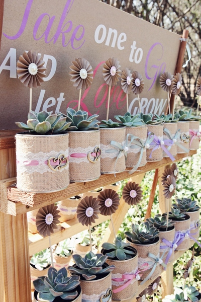 Old tins - made all beautiful with burlap, ribbon and pearls.  Rock roses used as a wedding favour - for each guest to go and plant once they are home.