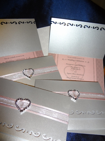 Custom wedding invitations - with punched edging, ribbon and trimmings.